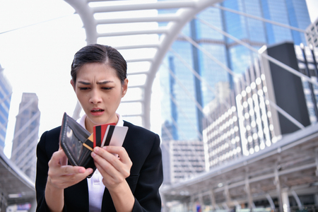 Concepto de desempleados. La empresaria asiática está abriendo la billetera vacía. La mujer de negocios joven está estresada porque no tiene dinero. Foto de archivo