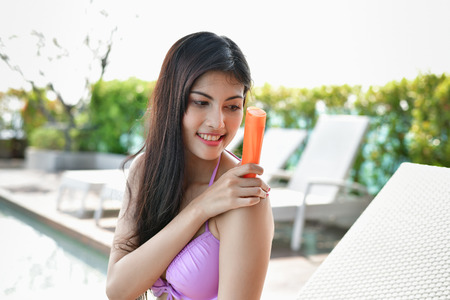 Swimsuit Concept. Beautiful girl in swimsuit is applying sunscreen. Beautiful girl in a swimsuit protects the skin from the sun with cream. beautiful girl apply sunscreen throughout the body.