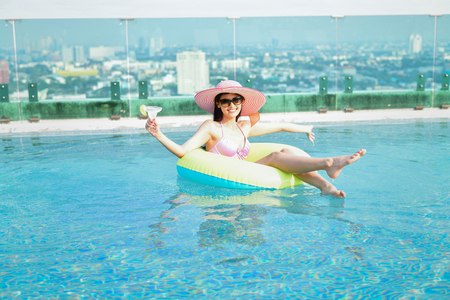 Swimsuit Concept. Beautiful girls in swimwear are drinking. Asian girls drink fruit juice at the pool. Beautiful girl in swimwear is happy at the pool.
