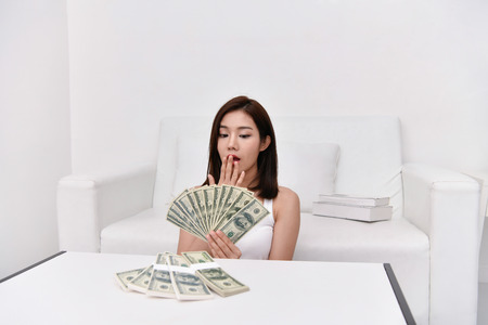 Financial concept. Beautiful girl is happy in her income. Beautiful women are counting money home.