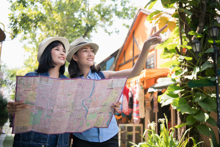 Travel Concept. Beautiful girls are happy to travel. Beautiful girls are finding a tourist spot on the map. Archivio Fotografico