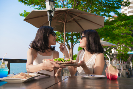 Leisure concept. Beautiful girl is eating at the seaside restaurant. Beautiful girl is enjoying the food on the table. 版權商用圖片