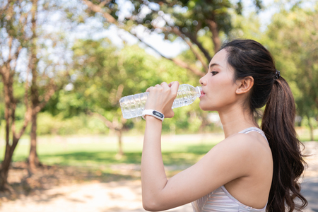 Exercise concept. Beautiful girl tired from exercise. Beautiful girl drinking water with thirst.