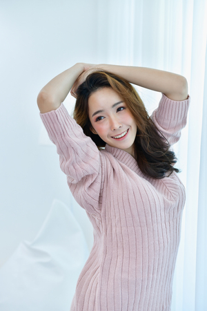 Winter Concept. Cute Asian girl in winter dress. Beautiful woman is relaxing in a bedroom. Beautiful women in winter clothes are waking up in the morning. Woman wearing a sweater in a white bedroom.