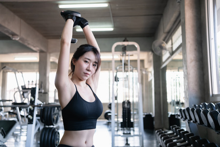 Exercise concept. A beautiful girl is exercising in the gym. Asian women are exercising with dumbbells. Imagens
