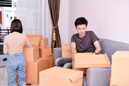 Moving house Concept. Asian young man is carrying his belongings. Young Asian women are holding their stuff in a paper box. Young are happy in the new house.