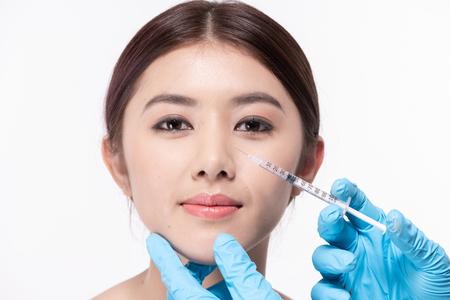 Chirurgie concept. De arts-cosmetoloog maakt de procedure voor verjongende gezichtsinjecties voor het aanscherpen en gladstrijken van rimpels op de gezichtshuid van een schoonheid.
