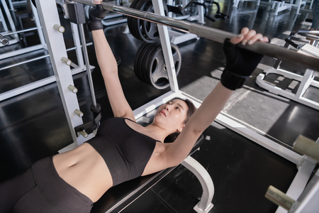 Exercise concept. A beautiful girl is exercising in the gym. Beautiful shapely girl because she plays barbell. Imagens