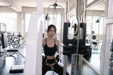 Exercise concept. A beautiful girl is exercising in the gym. A beautiful girl is playing a cable machine.