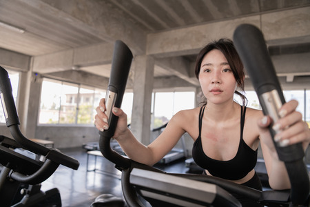 Exercise concept. Beautiful girl exercising with a spinning exercise bike. Beautiful girl exercising thighs for beautiful proportions. Imagens