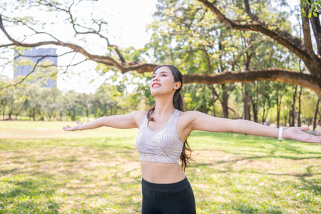 Concept of exercise. Beautiful girl stretching the muscles before running. Women exercising in the garden with freshness.