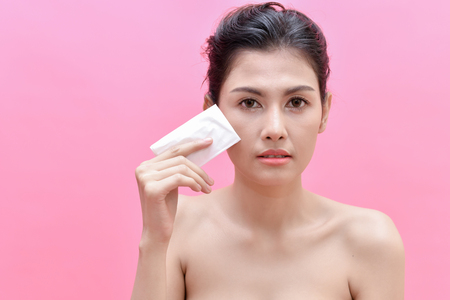 The concept of healthy beautiful woman. Beautiful women are experiencing skin problems. Beautiful Asian girl is using facial tissue on her face. Stock Photo