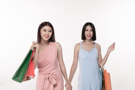 Shopping concept. Beautiful girl is carrying a bag on a white background. Asian girls are buying things happily.