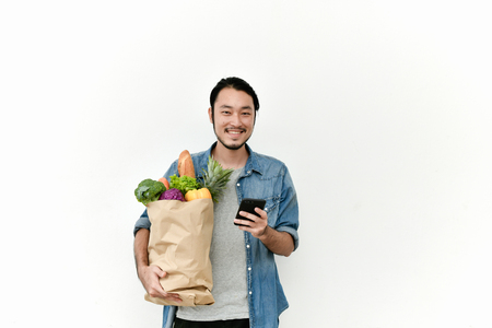Los hombres jóvenes están optando por comprar verduras por teléfono. El joven muestra la compra de verduras para la venta online.