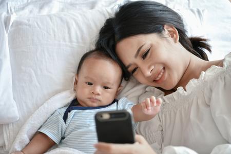 Concept nouveau-né. Mère et enfant sur un lit blanc. Maman et bébé garçon jouant dans la chambre. Mère joue au téléphone portable sur le lit.