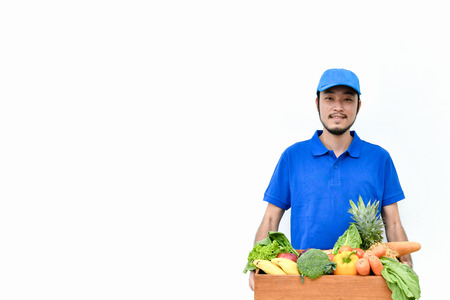Delivery concept. Delivery guy holding a bag of groceries isolated on white background.