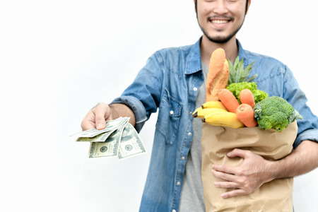 Young men choose fresh, clean fruits and vegetables. The young man is paying for the product.