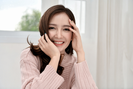 Relaxation concept. The beautiful girl is smiling happily inside the room. Beautiful Asian girl smiling cute and charming. Imagens