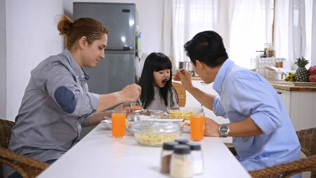 Family concept. The girl is eating food with her family.