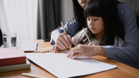 Family concept. Mom is teaching children to draw pictures. Stok Fotoğraf