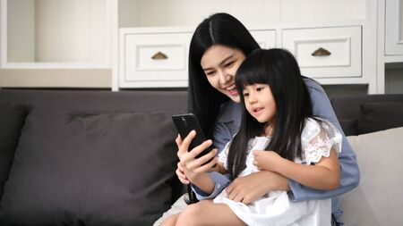 Communication concepts. Mother and daughter are watching TV programs on the internet. Banco de Imagens