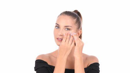 Notion de beauté. Soin de la peau. Femme enlevant l'huile du visage à l'aide de papiers buvards.