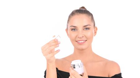 Beauty concept. Woman is opening a cream jar in her hand on a white background.