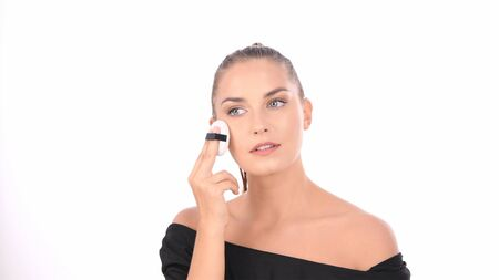 Beauty concept. Young woman applying blusher on her face with powder puff.