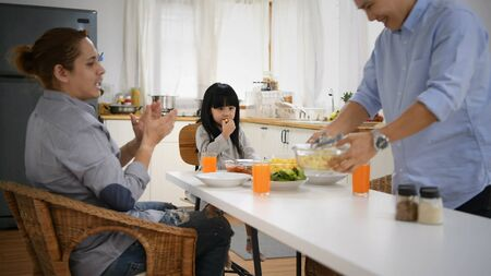 Family concept. Male couple and daughter dining in their kitchen