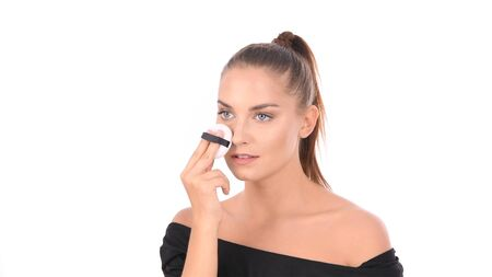 Beauty concept. The woman is using a sponge to apply powder on her face.