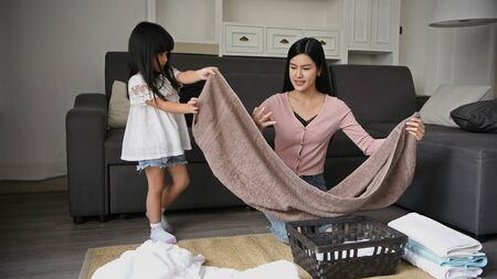 Family concept. Mother and daughter are folding clothes in the basket. Stockfoto