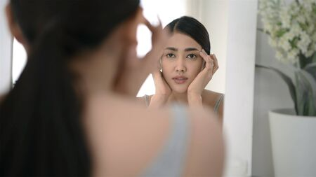 Beauty concept. A woman who looks at the mirror is having problems with irritated skin. Stockfoto - 150528666