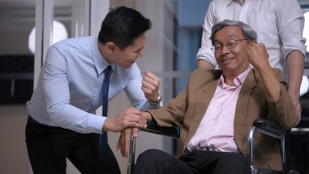 Health concept. Young men encourage old people in the office.