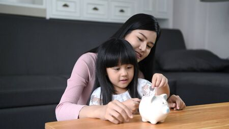 Financial concepts. The mother is teaching her daughter to know how to drop the piggy bank.