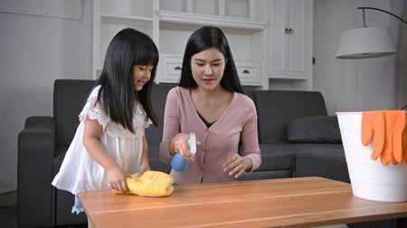 Concetto di pulizia. Madre e figlia aiutano a pulire la casa. Archivio Fotografico