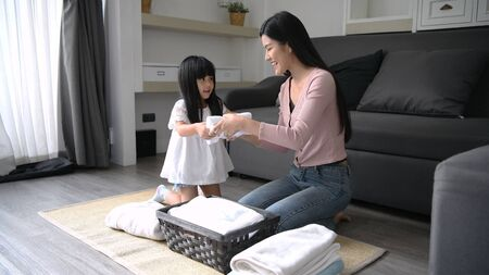 Concetto di famiglia. Madre e figlia stanno aiutando a fare i lavori di casa.