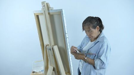 Artist Concept. A Middle aged women mixing colors on a plate on a white background. 4k Resolution.