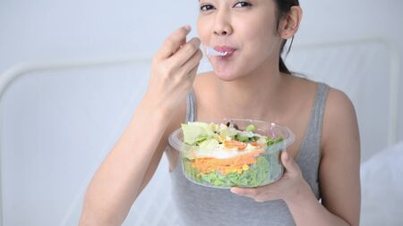 Health concept. Close up Asian girls are eating vegetables salad in the bedroom. 4k Resolution. Stock Photo