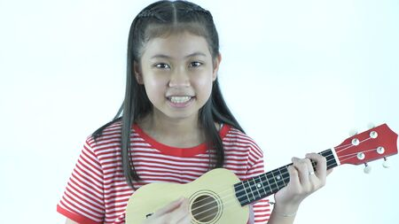 Young girls playing fun ukulele on a white background. 4k Resolution.