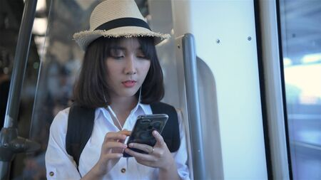 Tourism concept. An Asian girl is playing mobile on a train. 4k Resolution.