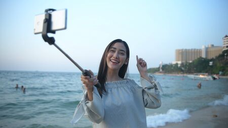 Holiday concept. Beautiful girl calling video on mobile to the beach. 4k Resolution. Standard-Bild - 134645287