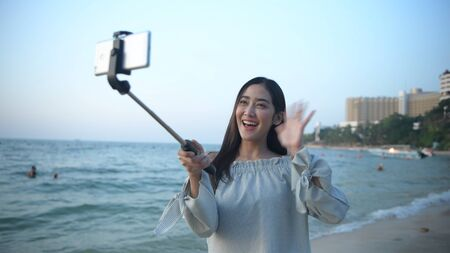 Holiday concept. Beautiful girl calling video on mobile to the beach. 4k Resolution. Standard-Bild - 134645303