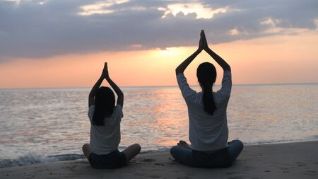 Silhouette of mother and daughter doing yoga by the sea in the evening. 4k Resolution. Stock Photo