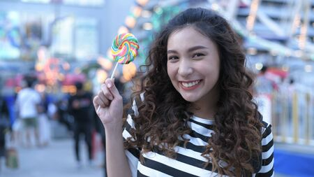 Holiday concept. Beautiful girls are eating lollipops happily in the amusement park. 4k Resolution.