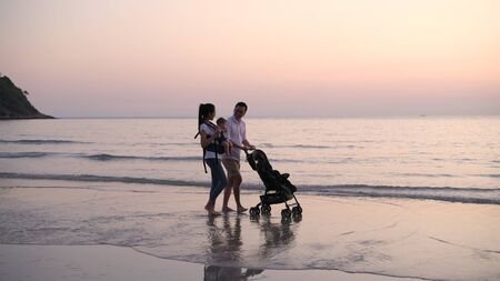 Holiday concept. Parents are pushing the baby cart on the beach. 4k Resolution.