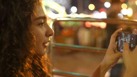 Holiday concept. A beautiful girl taking a high-angle photo on the ferris wheel. 4k Resolution.