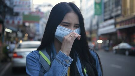 Concept of pollution prevention. A beautiful woman wearing a mask on the streets of the city. 4k Resolution.