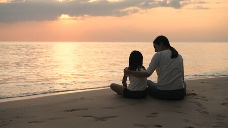 Holiday concept. Mother and daughter are watching the sunset on the beach. 4k Resolution.