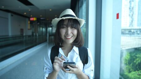 Tourism concept. A beautiful girl playing with a mobile phone in an airport. 4k Resolution.