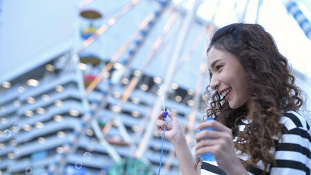 Holiday concept. Beautiful girls are playing soap bubbles in an amusement park. 4k Resolution.